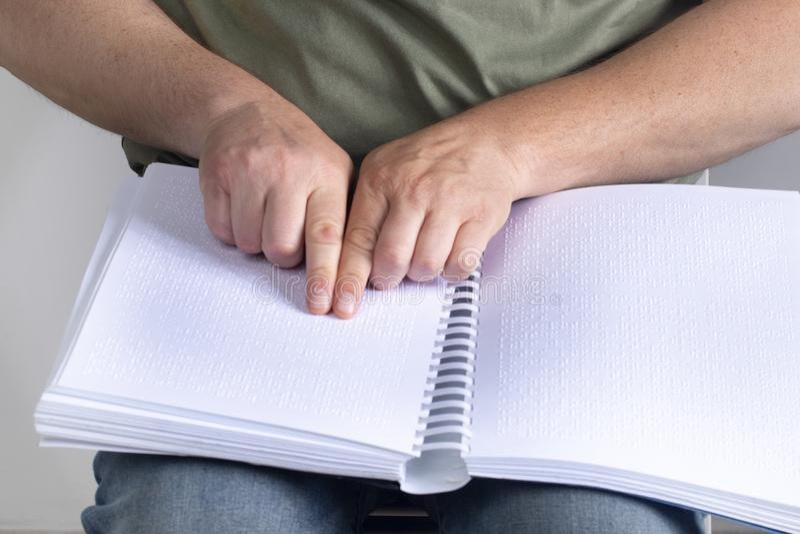 Den blinda mannen läste en skriftlig bok på blindskrift horisontal fotografering för bildbyråer