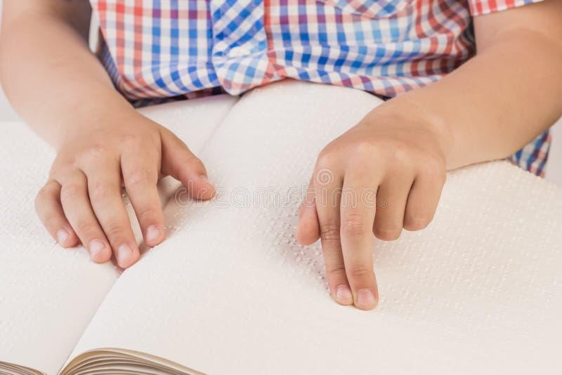 Den blinda pojken läser en skriftlig bok på blindskrift royaltyfri bild