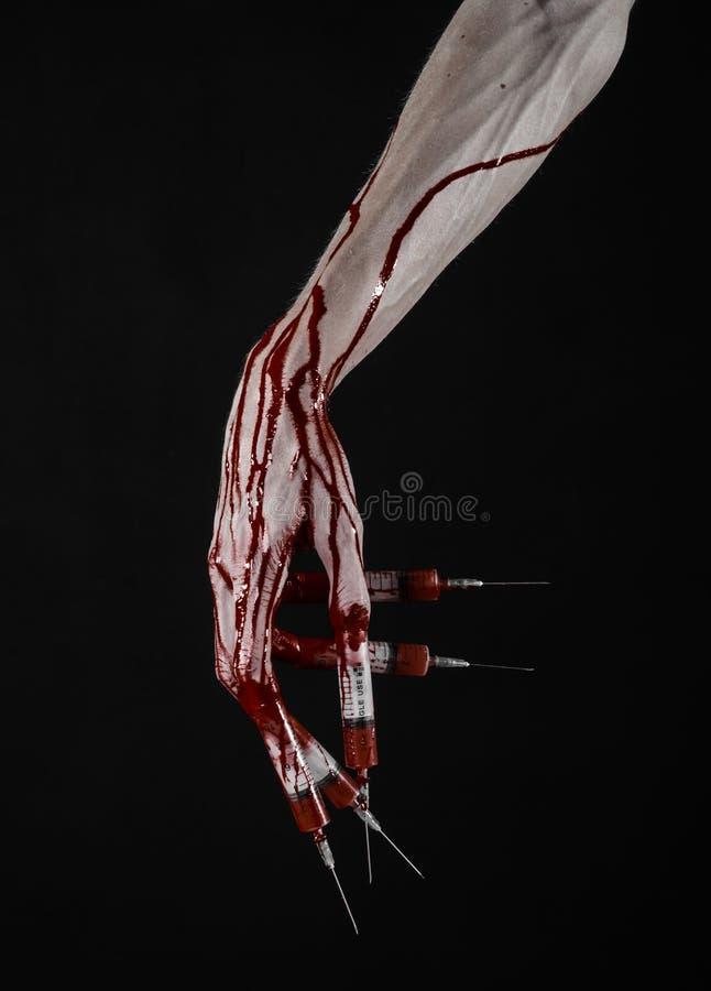 Den blodiga handen med injektionssprutan på fingrarna, tåinjektionssprutor, hand spolar ren, den förfärliga blodiga handen, det h arkivbild