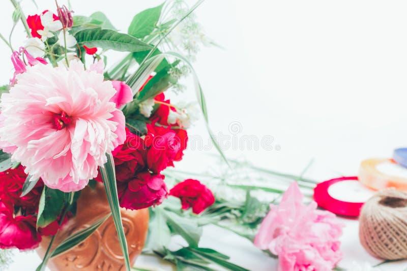 den blom- ordningen från härlig bukett av rosa färger blommar peons, blåklinter och röda rosor på vit bakgrund med utrymme för te royaltyfria foton