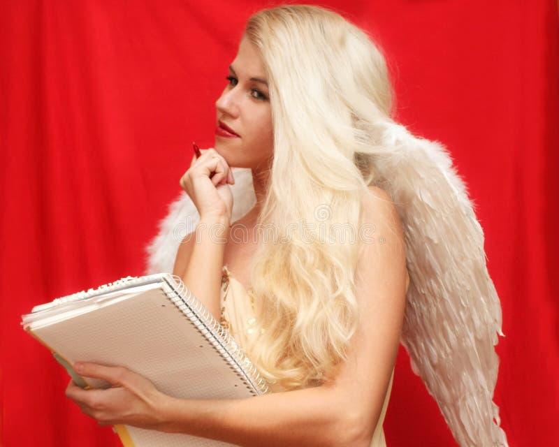 Den blonda ängeln skrivar ett brev På den röda bakgrunden royaltyfri foto