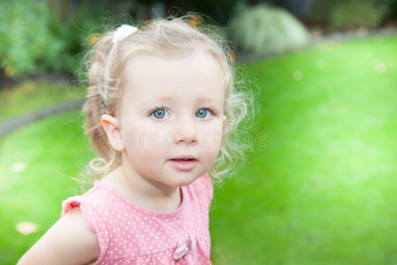 Den blonda barnflickan i grön trädgård parkerar utomhus royaltyfri foto