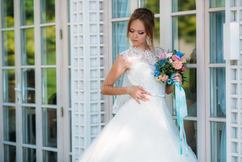 Den blonda bruden beundrar hennes spets- vita bröllopsklänning, undersöker broderi på kläder Flickahållna i henne hand a arkivfoto