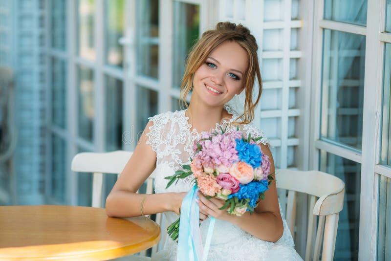 Den blonda bruden med ljusa blåa ögon ler i huvudsak En flicka med en blommabukett är lycklig att att gifta sig älskad fotografering för bildbyråer