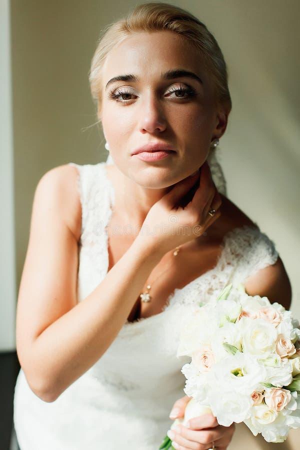 Den blonda bruden ser ursnyggt anseende i ljusen av middagsolen royaltyfria foton