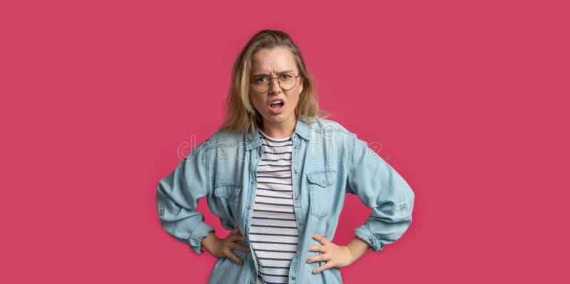 Den blonda chockade kvinnan ser med klagomål till den motsatta sidan som isoleras över rosa bakgrund arkivfoton