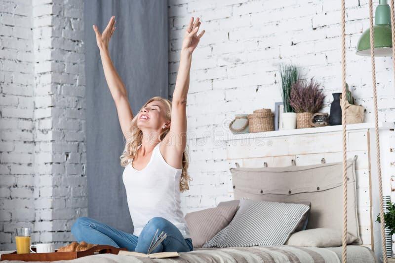 Den blonda damen sträcker på hennes säng i morgon arkivfoto