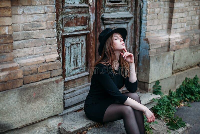 Den blonda drömma flickan med långt hår, i svart klänning i hatt, sitter på momenten på den gamla bakgrunden av tappningantikvite arkivbilder