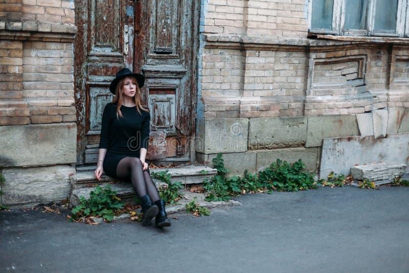 Den blonda eftertänksamma flickan med långt hår, i svart klänning i hatt, sitter på momenten på bakgrunden av gammalt trä för tap royaltyfri foto