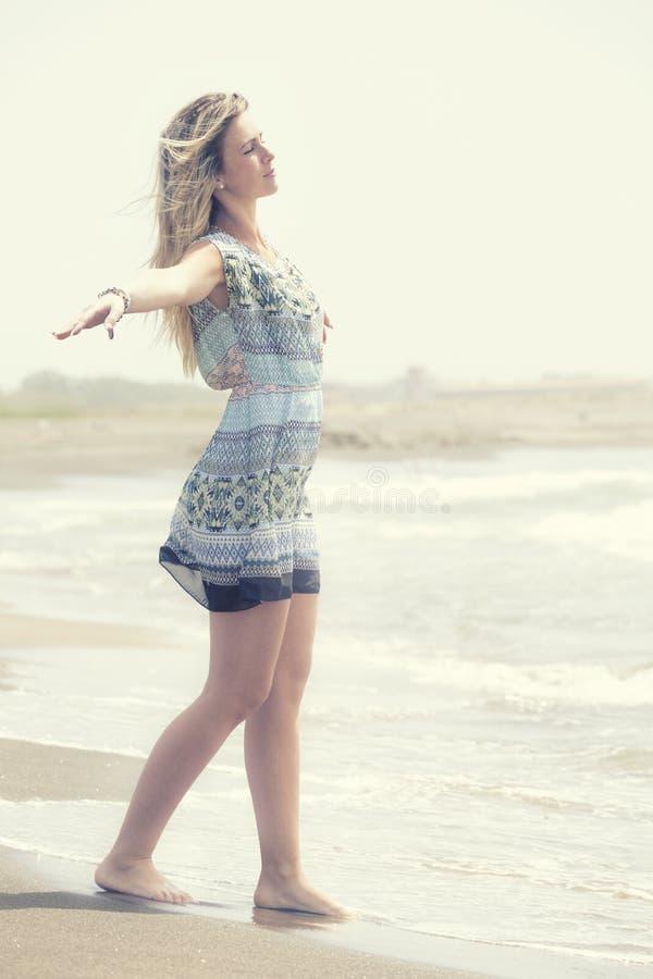 Den blonda flickaöppningen beväpnar utsträckt in mot havet arkivbild