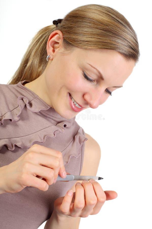 den blonda flickan henne spikar polering arkivfoto