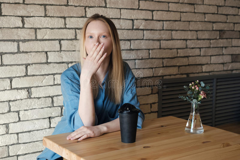 Den blonda flickan i en blå skjorta sitter på en tabell med ett exponeringsglas av kaffe som täcker henne, gömma i handflatan med royaltyfria bilder