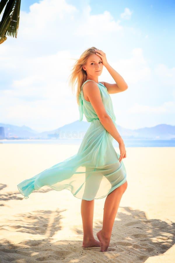 den blonda flickan i genomskinlig munkkåpa gömma i handflatan in skugga på stranden royaltyfri bild