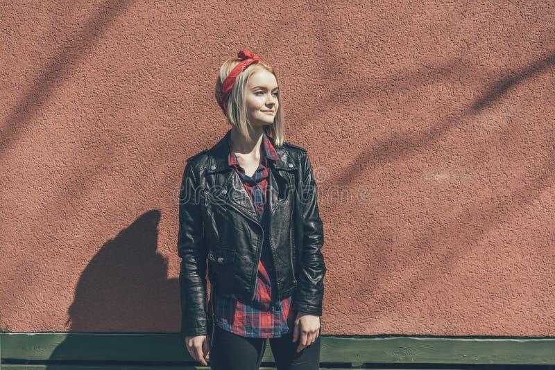 Den blonda flickan i rött hår förbinder och det svarta läderomslaget arkivbilder