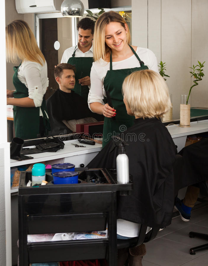 Den blonda flickan klipper hår av den mogna kvinnan på salongen royaltyfria foton