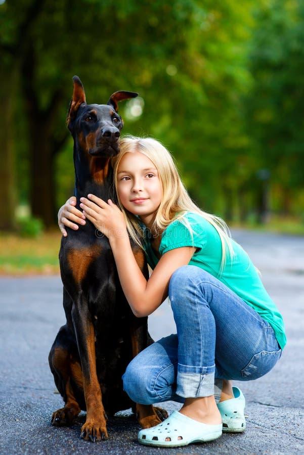 Den blonda flickan kramar hennes älskade hund eller doberman in arkivfoto