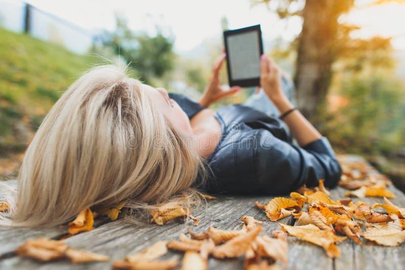 Den blonda flickan läser en bok från hennes ebooksavläsare fotografering för bildbyråer
