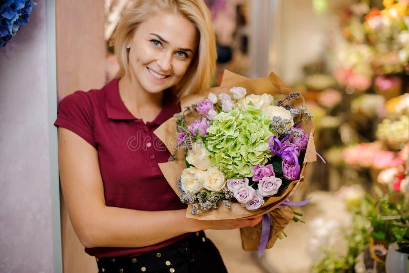 Den blonda flickan ler och rymmer i händer en stilfull bukett av rosor, vanliga hortensian och pioner arkivfoto