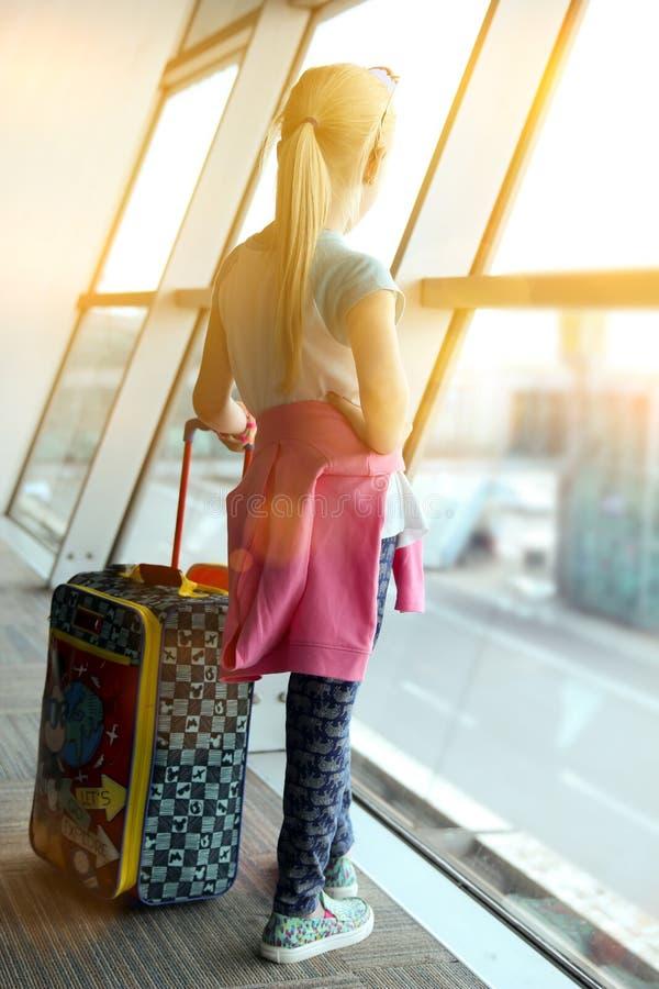 Den blonda flickan med bagage är det stående near fönstret på flygplatsen arkivbild