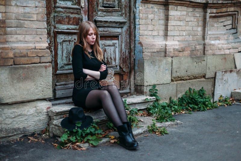 Den blonda flickan med långt hår, i svart klänning med en hatt i hans händer, sitter och fryser på momenten på bakgrunden av royaltyfri fotografi
