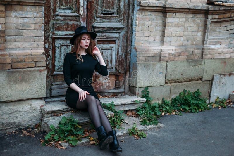 Den blonda flickan med långt hår, i svart klänning i hatt, sitter på momenten på bakgrunden av den antika gamla trädörren för tap arkivfoto