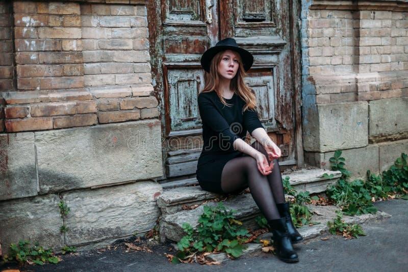 Den blonda flickan med långt hår, i svart klänning i hatt, sitter på momenten på bakgrunden av den antika gamla trädörren för tap royaltyfria foton
