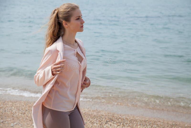 Den blonda flickan promenerar stranden av havskusten fotografering för bildbyråer