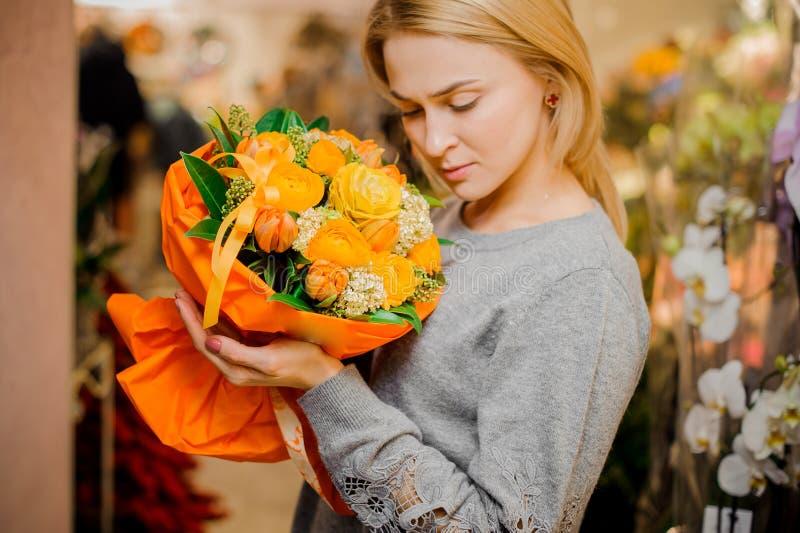 Den blonda flickan rymmer en bukett av orange rosor och tulpan arkivbilder