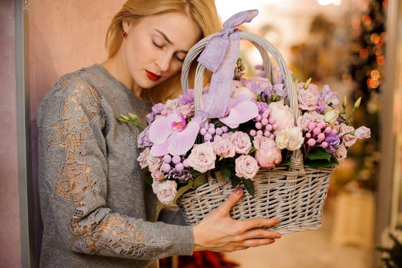 Den blonda flickan rymmer en korg av purpurfärgade blommor inklusive rosor och orkidér arkivbild
