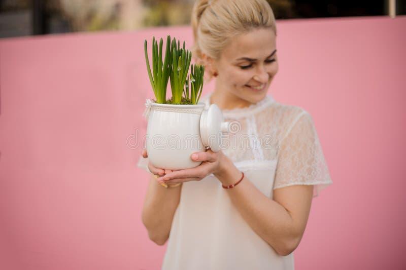 Den blonda flickan rymmer växten i blomkruka arkivbild