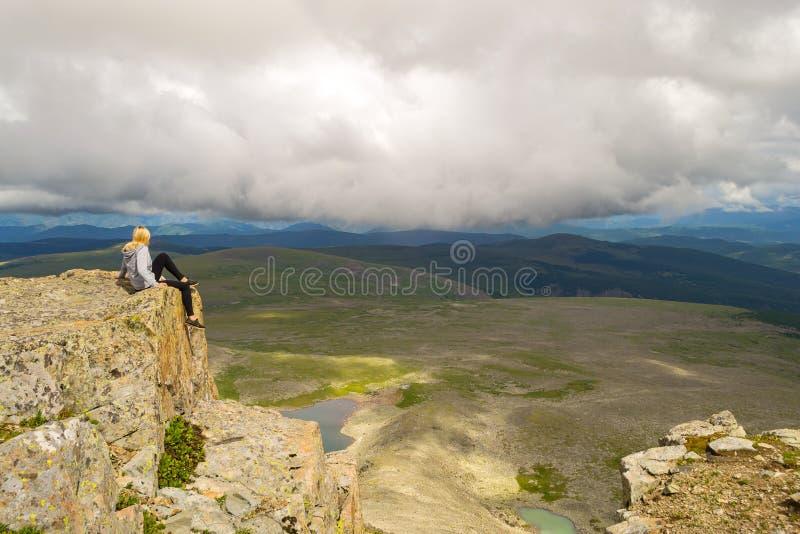 Den blonda flickan sitter bara på kanten av klippan ovanför aben arkivbild
