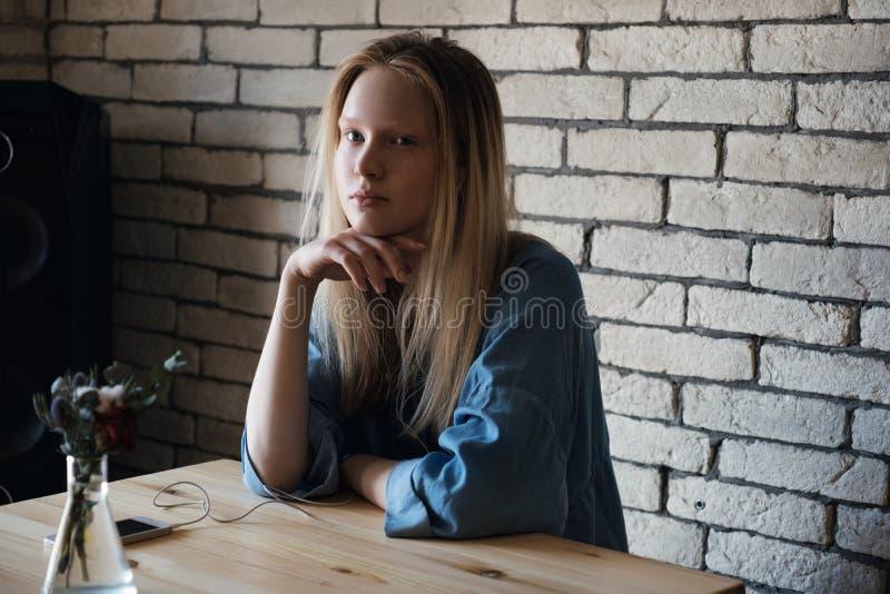 Den blonda flickan sitter med hörlurar och ser hänsynsfullt bort, med hennes hand på hennes haka royaltyfri bild