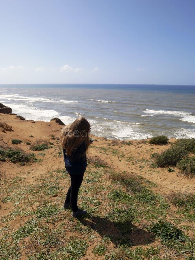 Den blonda flickan står med en smartphone arkivbilder
