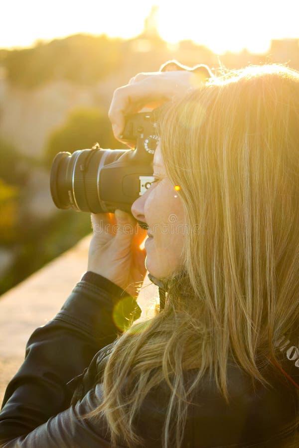 Den blonda flickan tar foto med reflex royaltyfria foton