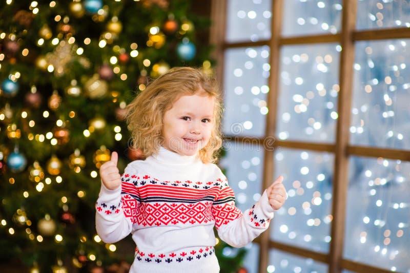 Den blonda flickavisningen tummar upp på bakgrunden av jultre royaltyfri bild