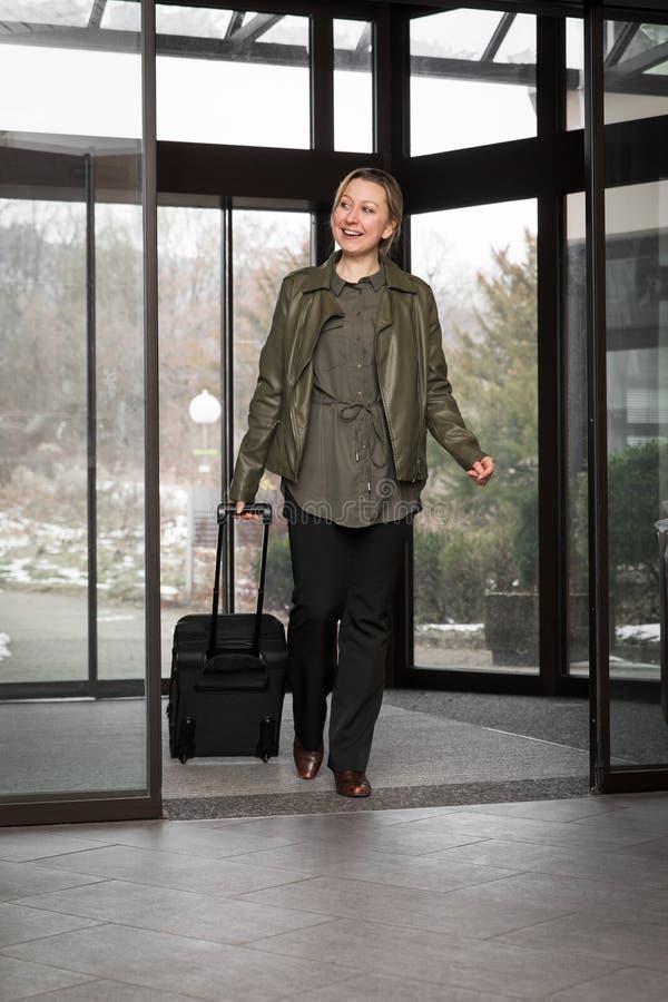 Den blonda gästen ankommer i en hotelllobby arkivbilder