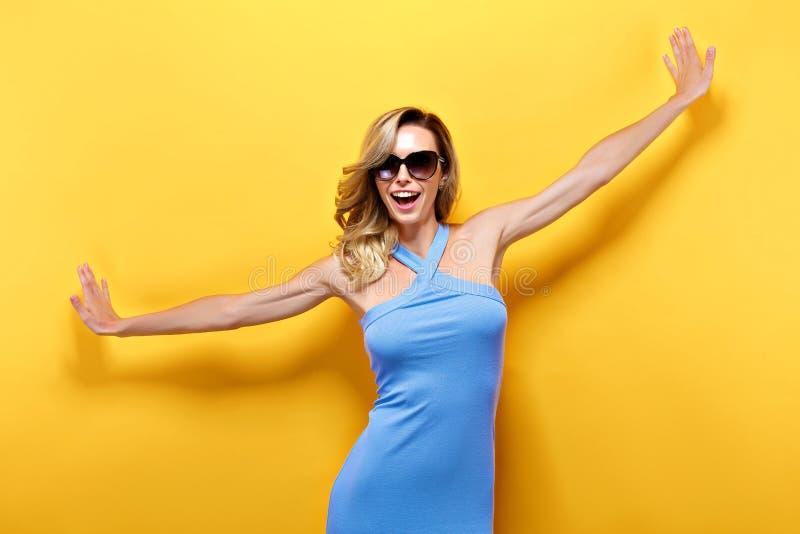 Den blonda gladlynta modellen i blått klär med utsträckta armar royaltyfria bilder