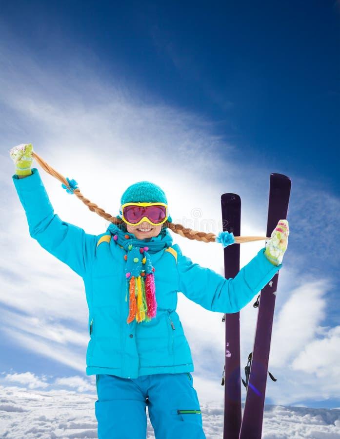 Den blonda gulliga flickan skidar på vintersemestern royaltyfri foto