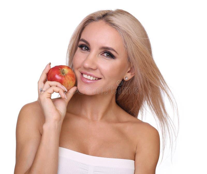 Den blonda kvinnan äter det röda äpplet fotografering för bildbyråer