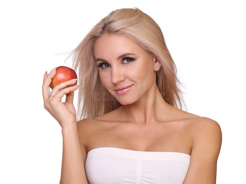 Den blonda kvinnan äter det röda äpplet arkivfoton