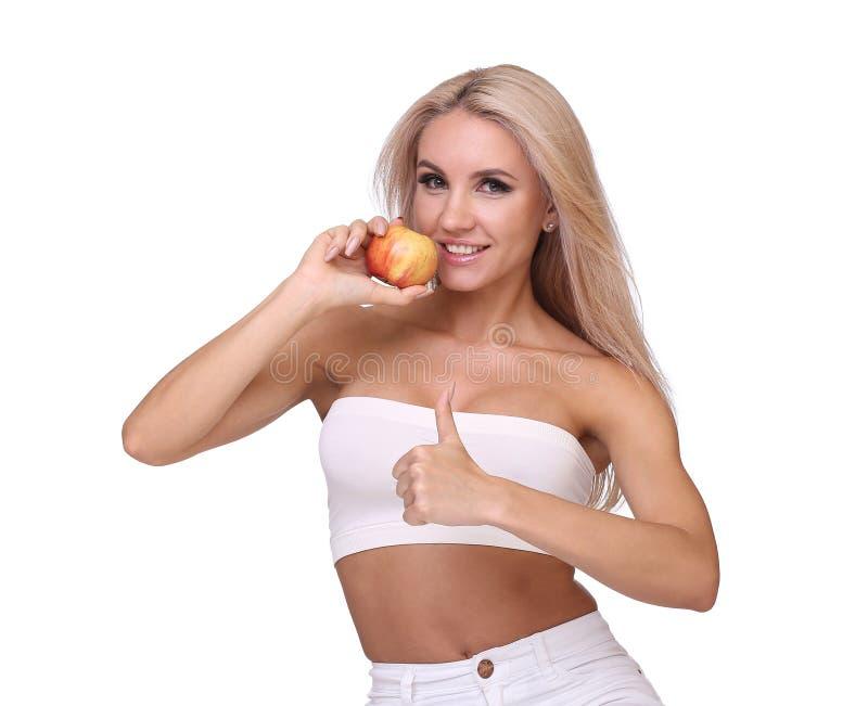 Den blonda kvinnan äter det röda äpplet royaltyfri foto