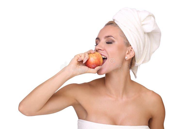 Den blonda kvinnan äter det röda äpplet arkivbild