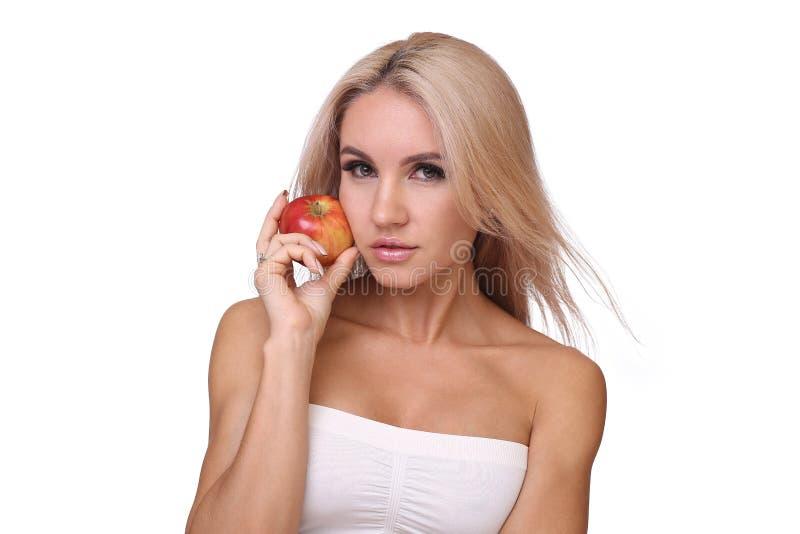 Den blonda kvinnan äter det röda äpplet arkivbilder