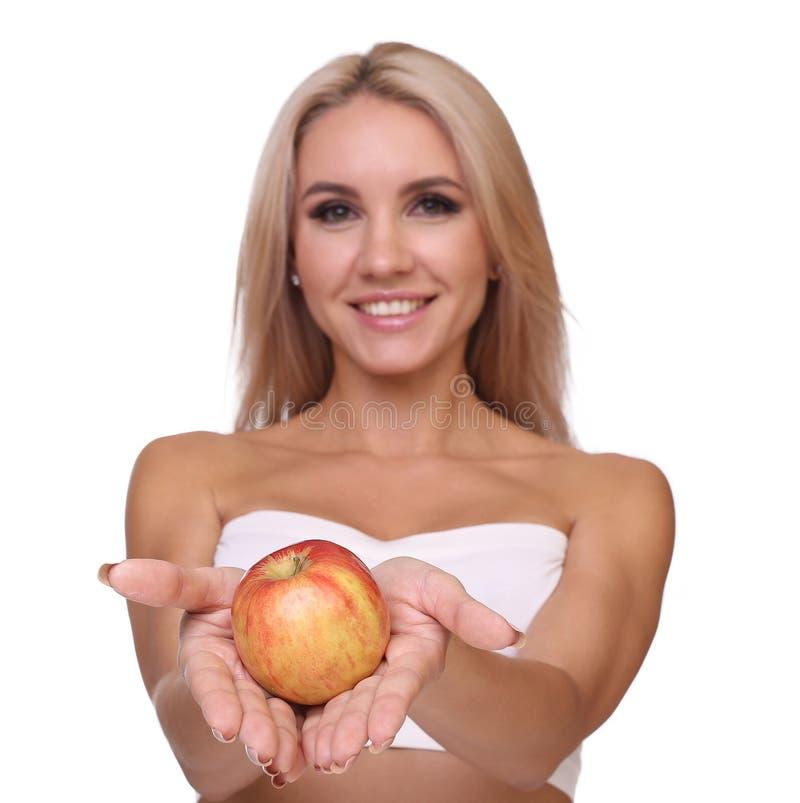 Den blonda kvinnan äter det röda äpplet arkivfoto