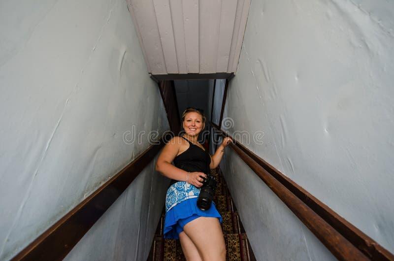 Den blonda kvinnan går upp trappan på en kuslig trappuppgång i en spökstad i Wyoming arkivbilder