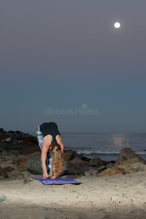 Den blonda kvinnan i modellstrumpbyxor som utför knäsena, sträcker på natten royaltyfri foto