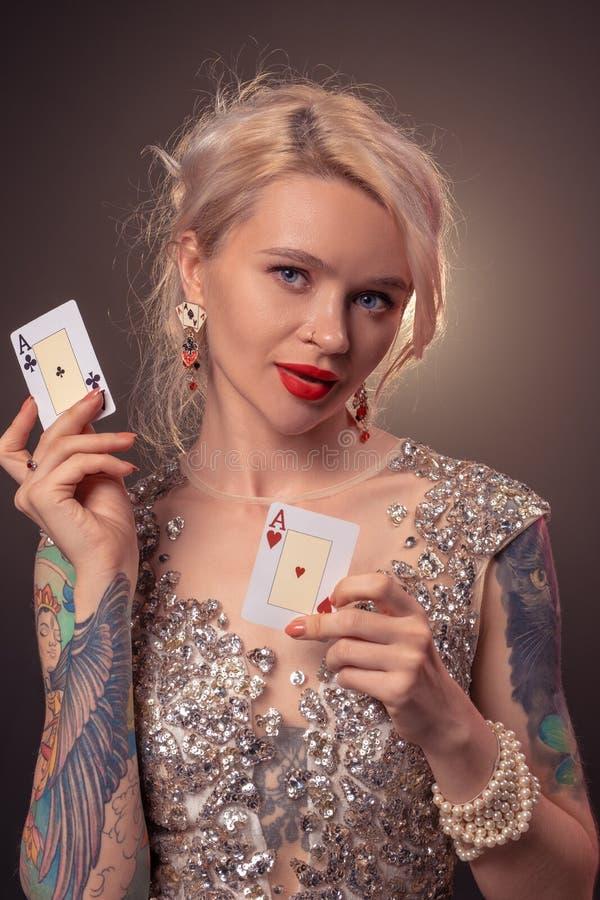 Den blonda kvinnan med en härlig frisyr och ett perfekt smink poserar med spela kort i hennes händer Kasino poker fotografering för bildbyråer