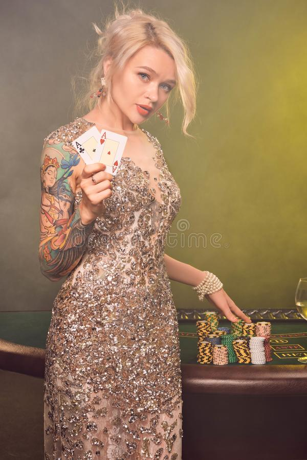 Den blonda kvinnan med en härlig frisyr och ett perfekt smink poserar med två spela kort i hennes händer Kasino poker arkivbilder