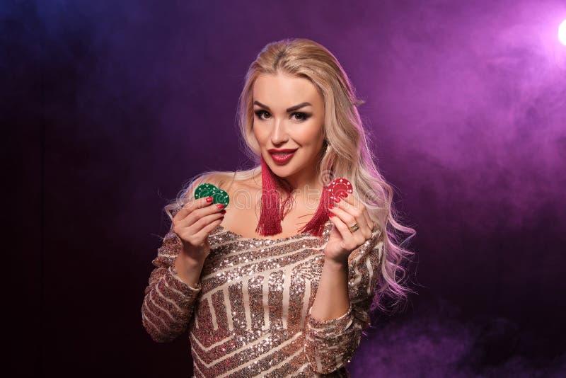 Den blonda kvinnan med en perfekt frisyr och ett ljust smink poserar med dobblerichiper i hennes händer Kasino poker royaltyfria bilder