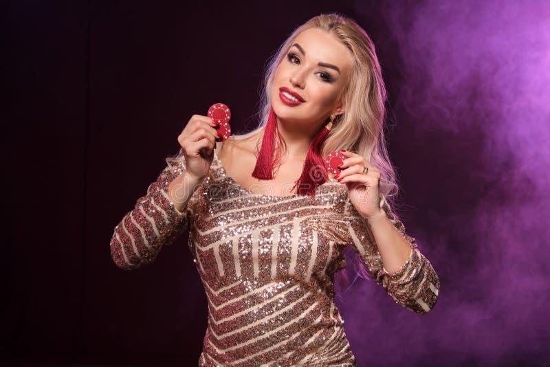 Den blonda kvinnan med en perfekt frisyr och ett ljust smink poserar med dobblerichiper i hennes händer Kasino poker arkivbilder